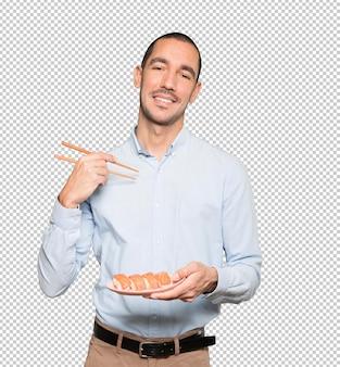 Jeune homme à l'aide de baguettes pour manger des sushis