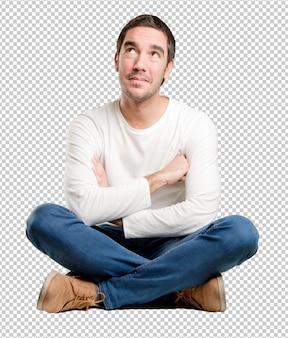 Jeune homme assis avec un geste de doute