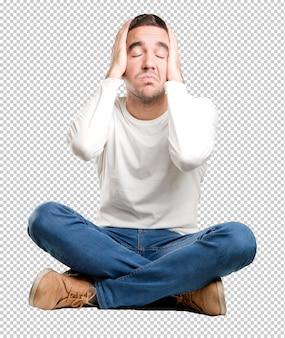 Jeune homme assis avec un geste fatigué