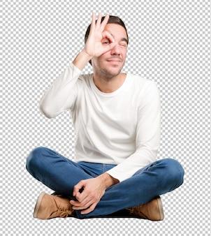 Jeune homme assis avec un geste d'observation