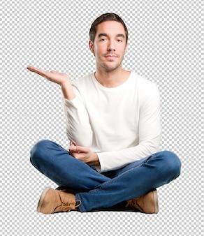 Jeune homme assis avec geste de spectacle