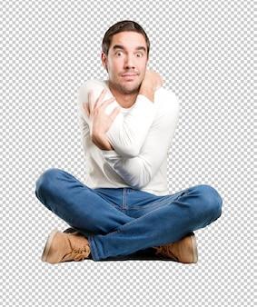 Jeune homme assis avec un geste de stress