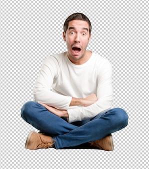 Jeune homme assis avec un geste de surprise