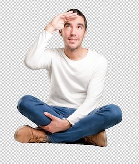 Jeune homme assis avec un geste de la vue