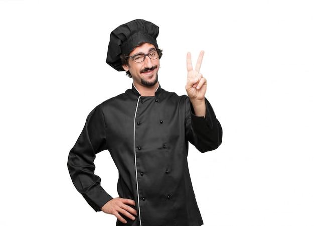 Jeune homme chef souriant et regardant satisfait et heureux, comptant le numéro deux avec les doigts