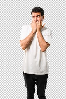 Un jeune homme avec une chemise blanche est un peu nerveux et a peur de mettre ses mains à la bouche