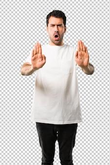 Jeune homme avec une chemise blanche faisant un geste d'arrêt avec sa main pour déçu par un avis