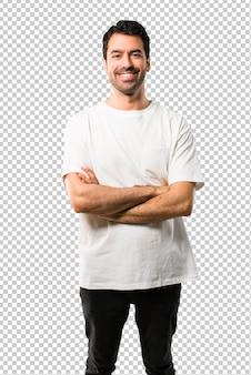 Jeune homme avec une chemise blanche, gardant les bras croisés en position frontale. expression confiante