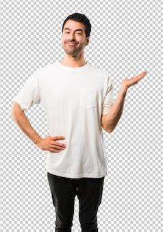 Jeune homme avec une chemise blanche tenant une surface imaginaire sur la paume pour insérer une annonce
