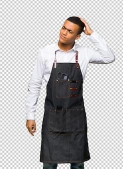 Jeune homme de coiffeur afro-américain ayant des doutes tout en grattant la tête