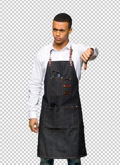 Jeune homme de coiffeur afro-américain montrant le pouce vers le bas de signe avec une expression négative