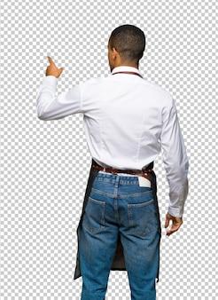 Jeune homme de coiffeur afro-américain pointant en arrière avec l'index