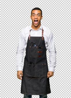 Jeune homme de coiffeur afro-américain avec surprise et expression faciale choquée