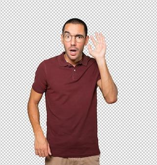 Jeune homme concentré faisant un geste pour essayer d'entendre quelque chose