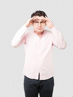 Jeune homme concentré avec un geste de regarder ailleurs