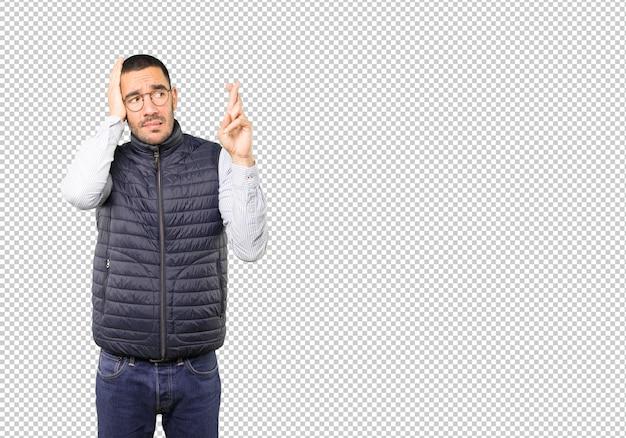 Jeune homme concerné faisant un geste des doigts croisés