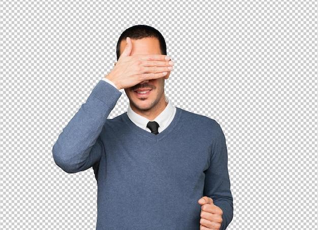 Jeune homme couvrant ses yeux avec ses mains
