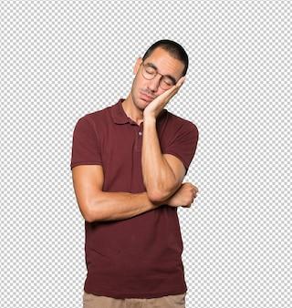 Jeune homme détendu faisant un geste de sommeil