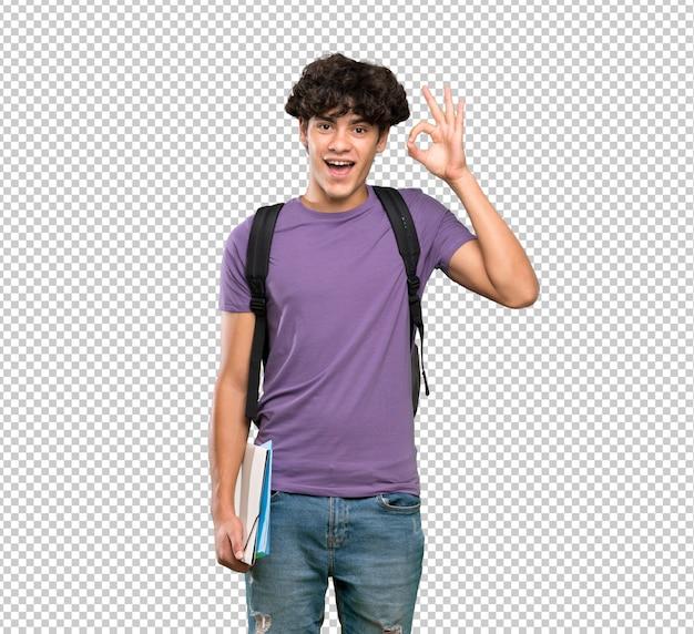 Jeune homme étudiant surpris et montrant un signe ok