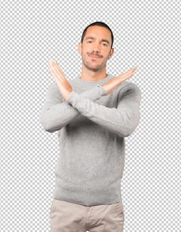 Jeune homme faisant un geste de ne pas traverser avec les bras