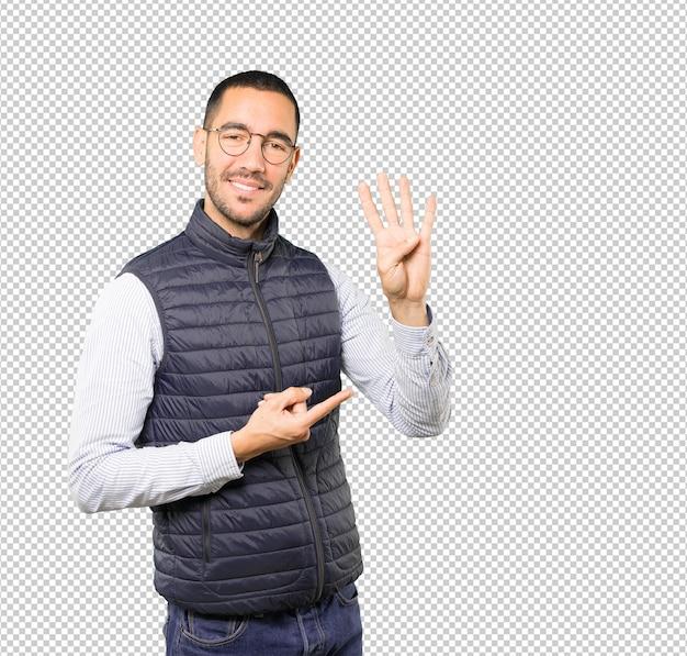 Jeune homme faisant un geste numéro quatre