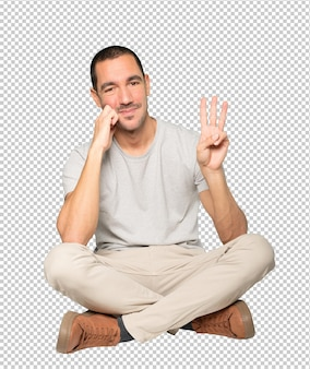 Jeune homme faisant un geste numéro trois