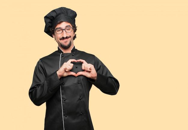 Jeune homme fou en tant que chef souriant, regardant heureux et amoureux, faisant la forme d'un coeur avec les mains