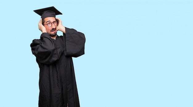 Jeune homme gradué avec les deux mains couvrant les oreilles pour les protéger d'un son inconfortable, bruyant et gênant