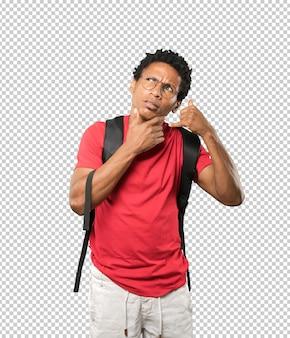 Jeune homme hésitant faisant un geste d'appel avec la main