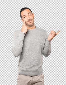 Jeune homme hésitant faisant un geste d'être prudent avec sa main pointant vers son œil
