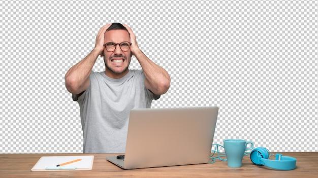 Jeune homme inquiet assis à son bureau