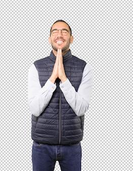 Jeune homme inquiet priant le geste