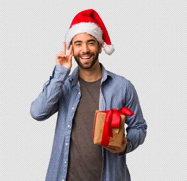 Jeune homme portant le bonnet de noel amusant et heureux faisant un geste de victoire