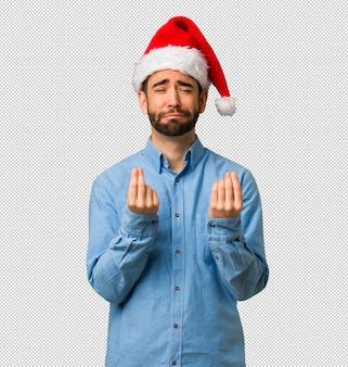 Jeune homme portant le bonnet de noel faisant un geste de nécessité