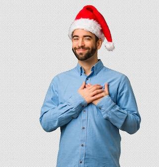 Jeune homme portant le bonnet de noel faisant un geste romantique