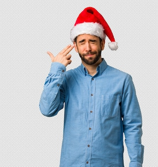 Jeune homme portant le bonnet de noel faisant un geste de suicide