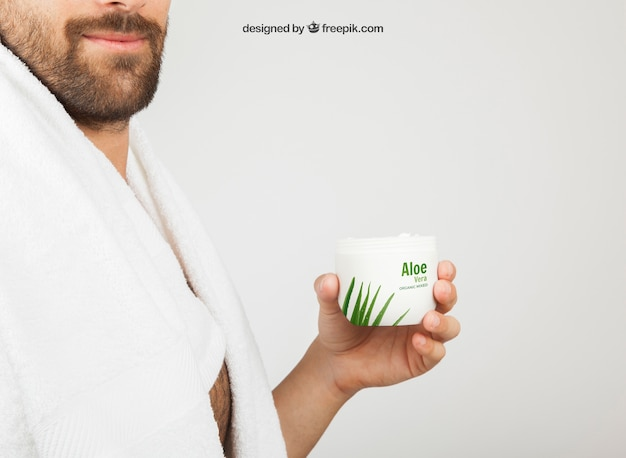 Jeune homme posant avec le produit cosmétique d'aloe vera