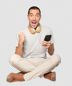Jeune homme en position assise avec un geste de célébration