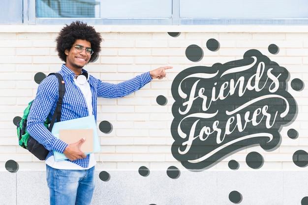 Jeune homme souriant pointant le message positif