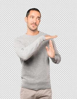 Jeune homme stressé faisant un geste de temps mort avec ses mains