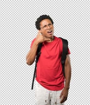 Jeune homme surpris faisant un geste d'appel avec la main
