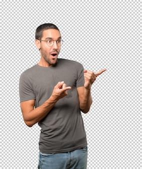 Jeune homme surpris pointant vers vous avec son doigt