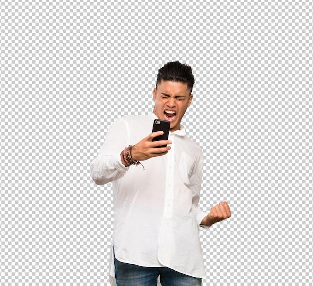 Jeune homme avec téléphone en position de victoire