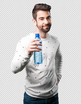 Jeune homme tenant une bouteille d'eau