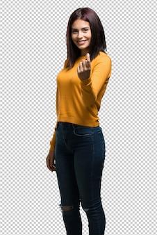 Jeune jolie femme invitant à venir, confiante et souriante faisant un geste de la main, étant positive et amicale