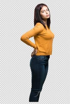 Jeune jolie femme avec des maux de dos dus au stress au travail, fatiguée et astucieuse