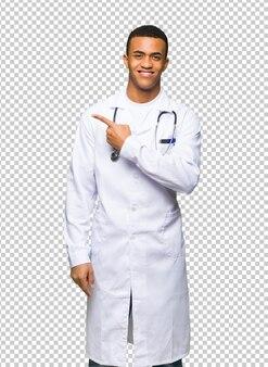 Jeune médecin afro-américain pointant sur le côté pour présenter un produit
