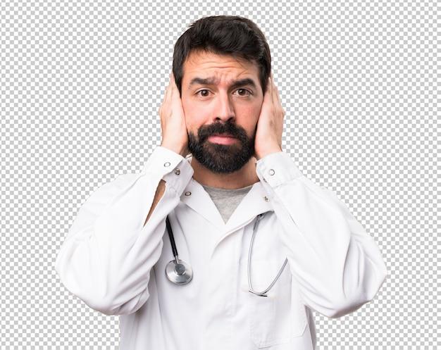Jeune médecin couvrant ses oreilles