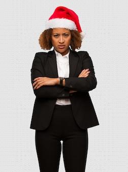 Jeune, noir, femme affaires, porter, noël, santa, chapeau, croisement bras, détendu