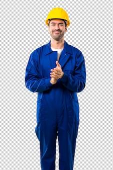 Jeune ouvrier avec casque applaudissant après la présentation à une conférence